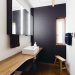 洗面室は、既存の床に合わせたカウンターを作りました。他の空間とは異なる白壁とソフトブラックのコントラストで木質のカウンターが引き立つすっきりと清潔感のあるスペースになりました