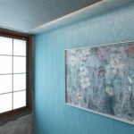 剥き出しのRCに囲まれた中、一面だけクロスを貼り床の間のイメージに。彩度を抑えたブルーグリーン色で絵や掛け軸が映える壁面。